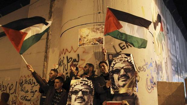 Palestinians hold posters with an image of the late Palestinian leader Yasser Arafat and wave Palestinian flags during a rally opposite to part of Israel's controversial barrier in the West Bank city of Bethlehem November 29, 2012. (Ammar Awad/REUTERS)