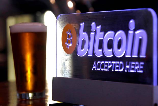 A Bitcoin sign on display at a bar in central Sydney, Australia. Some critics say bitcoin is not an actual currency because it doesn't reliable hold value and cannot be spent easily.