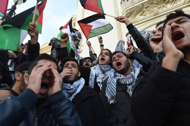 Tunisian demonstrators shout slogans and wave Palestinian flags during a demonstration in Tunis.