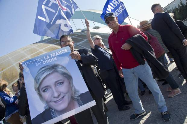 Supporters of far-right leader and candidate for the 2017 French presidential election Marine Le Pen hold flags and a poster as they wait outside to attend a meeting in Marseille, southern France, on April 19, 2017.
