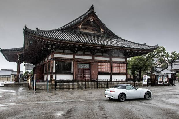 A Japan-spec Mazda MX-5 sits outside of a temple in Kyoto.