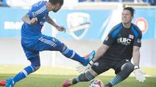 Montreal Impact's Andres Romero, left, scores against New England Revolution's Bobby Shuttleworth during first half MLS soccer action in Montreal, Saturday, May 31. (Graham Hughes/THE CANADIAN PRESS)