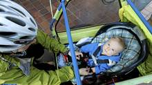 Amanda Beernink buckles up her son Tayo, 9 months, to go for an early bike ride Thursday morning in Vancouver, BC. Photo: Laura Leyshon for the Globe and Mail (Laura Leyshon for the Globe and)