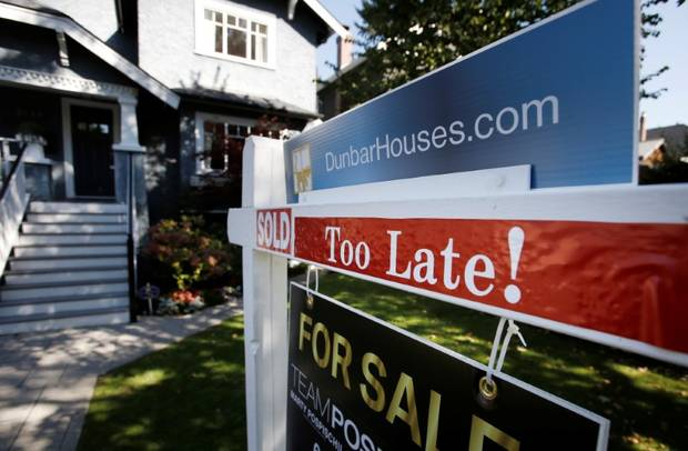 A real estate for sale sign is pictured in front of a home in Vancouver.