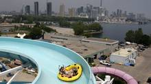 Toronto, July 07 2010 The skyline of Toronto under Smog and humidex advisories can be seen from the top of the water slide at Ontario Place on Lakeshore Blvd., while visitors (L to R) Riley Lardner, Mackenzie Little and Madison Lardner, enjoy a ride in the hot weather. Photo by: Fernando Morales/The Globe and Mail (Fernando Morales/The Globe and Mail)