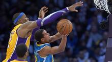Los Angeles Lakers centre Dwight Howard, left, blocks the shot of New Orleans Hornets guard Brian Roberts during the second half of their NBA basketball game, Tuesday, Jan. 29, 2013, in Los Angeles. (Associated Press)