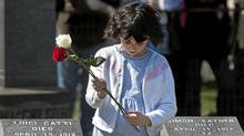 A child holds a flower that will be placed on a grave marker at a memorial service at Fairview Lawn Cemetery to mark the 100th anniversary of the sinking of RMS Titanic in Halifax on Sunday, April 15, 2011. (Andrew Vaughan/The Canadian Press/Andrew Vaughan/The Canadian Press)