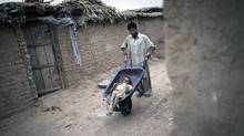 A Pakistani man wheels a child, Jamshid, 8, who suffers from polio on the outskirts of the capital Islamabad on July 6, 2011. (Behrouz Mehri/AFP/Getty Images/Behrouz Mehri/AFP/Getty Images)