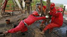 Labourers work at a well head in a PetroChina oil field in Tongnan, southwest China's Sichuan province. (STRINGER SHANGHAI)