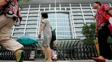 Shoppers walk past the headquarters of the Industrial and Commercial Bank of China in Beijing Wednesday July 19, 2006. (GREG BAKER/AP/GREG BAKER/AP)