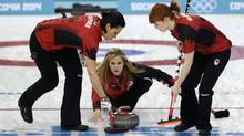 Canada's skip Jennifer Jones, centre, delivers the rock to her sweepers Jill Officer, left, and Dawn McEwen during women's curling competition against Great Britain at the 2014 Winter Olympics, Wednesday, Feb. 12, 2014, in Sochi, Russia. (Robert F. Bukaty/AP)
