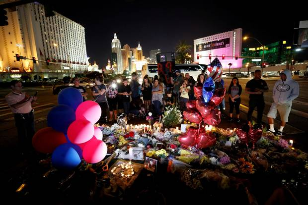 People gather at a makeshift memorial in the middle of Las Vegas Boulevard.