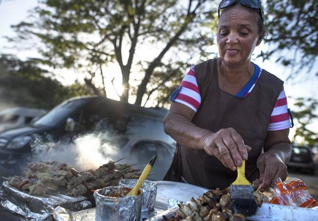 Mary, a street food vendor, cooks and sells grilled chicken and pork on Calle Central.