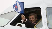 Prime Minister Stephen Harper waves a Conservative party flag from the cockpit of his campaign plane as he arrives in Ottawa,Tuesday May 3, 2011. (Adrian Wyld)