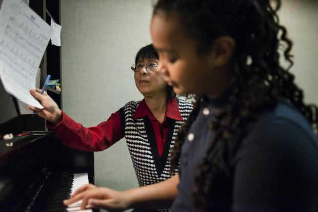 Henriette Nguyen instructs Rediat Ghebru, 10, on the piano.