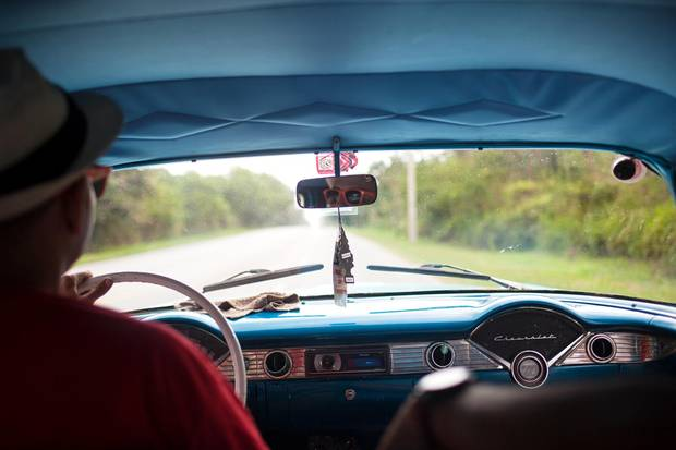 A view of the highway outside of Havana. The Cuban government allows individual Cubans to work privately driving restored antique cars for tourists. Yadir, pictured here, and a driver hired by the photographer had been driving this 1956 Chevy privately for three years.