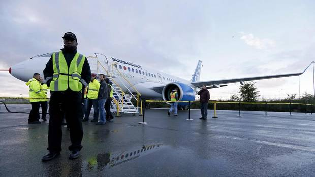 Bombardier employees at the C Series test aircraft prior to its first flight in Mirabel, Que., Sept. 16, 2013. The aircraft is the first all-new-design narrow-body plane in its class in decades. (CHRISTINNE MUSCHI/REUTERS)