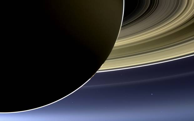 On July 19, 2013, NASA's Cassini spacecraft slipped into Saturn's shadow and turned to image the planet, seven of its moons, its inner rings -- and, in the background, our home planet, Earth - the tiny white dot at lower right.