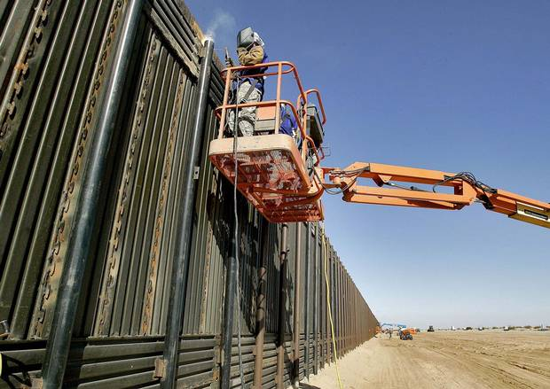 National Guardsmen weld a section of wall being erected along the international border that separates San Luis, Mexico, and San Luis, Arizona, in 2007.