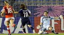 Switzerland's goalkeeper Nadine Boeni (12) saves the ball shot by Japan's forward Kumi Yokoyama (10) as Swiss midfielder Natasha Gensetter (18) follows during their Group A match at the U20 women's World Cup soccer tournament in Tokyo Sunday, Aug. 26, 2012. (Associated Press)