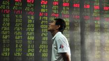 An investor looks at a monitor (not seen) in front of an electronic board showing stock information at a brokerage house in Shenyang, Liaoning province Aug. 15, 2012. Shanghai shares sank to their lowest in almost two weeks. (SHENG LI/REUTERS)