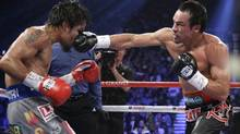 Juan Manuel Marquez, from Mexico, right, lands a right to the head of Manny Pacquiao, from the Philippines, during their WBO world welterweight fight Saturday, Dec. 8, 2012, in Las Vegas. (Julie Jacobson/AP)