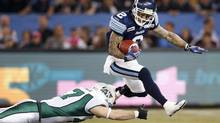 Toronto Argonauts kick receiver Chad Owens (R) runs the ball against Saskatchewan Roughriders' Cory Huclack (L) during the first half of their CFL game in Toronto October 8, 2012. (MARK BLINCH/REUTERS)