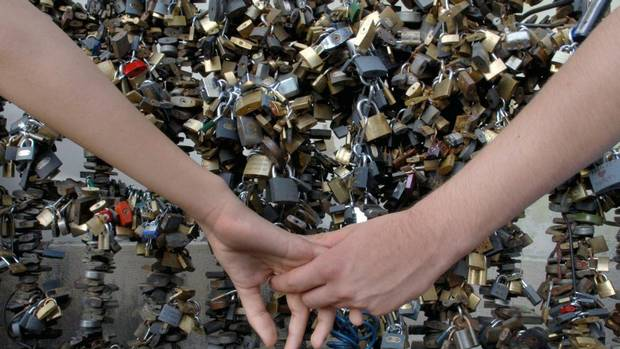 Lovers seal their relationship with a padlock on bridges around the globe. (BELA SZANDELSZKY/AP)