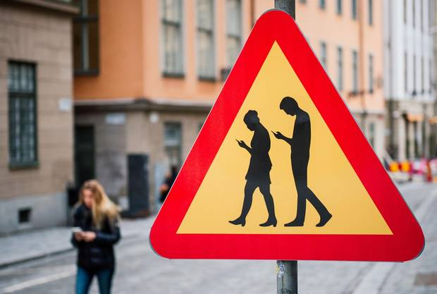 A road sign warning against pedestrians focusing on their smartphones in Stockholm in 2016.