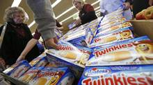 "Customers grab boxes of Hostess Brands ""Twinkies"" in a Chicago store. (JIM YOUNG/REUTERS)"