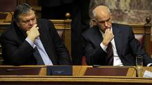 Greek Prime Minister George Papandreou (R) and Finance Minister Evangelos Venizelos wait for the result of the confidence vote at the Greek Parliament in Athens early on November 5, 2011. Greek Prime Minister George Papandreou won a nail-biting confidence vote after pledging to initiate the talks to overcome a budding revolt from the party founded by his father nearly four decades ago. Greece on Saturday was to begin talks on forming an emergency government to drag itself out of political stalemate caused by two years of austerity as the shadow of bankruptcy loomed over the crisis-hit nation. (LOUISA GOULIAMAKI/AFP/Getty Images/LOUISA GOULIAMAKI/AFP/Getty Images)