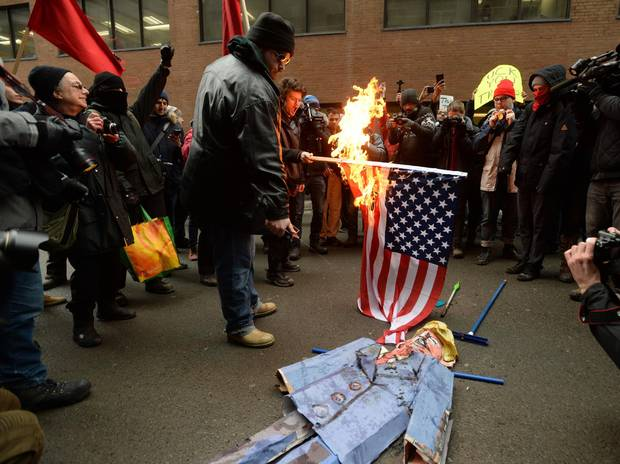 Anti-Trump protesters burn an effigy of Donald Trump in the streets of Montreal on Friday.