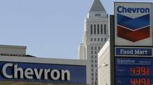 In this Thursday, Jan. 26, 2012 photo, higher than locally average gas prices are digitally displayed at a Chevron gas station downtown Los Angeles. Chevron says Friday, Jan. 27, 2012 that its net income slipped 3.2 percent in the fourth quarter as its refineries struggled to pass on the higher cost of crude oil. (AP Photo/Damian Dovarganes) (Damian Dovarganes/AP)