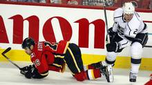 The Los Angeles Kings' Matt Grenne knocks the Calgary Flames Tom Kostopoulos to the ice in Calgary. (Jeff McIntosh/Jeff McIntosh/The Canadian Press)