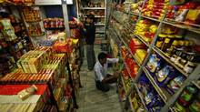 Indian workers arrange packets of food at a grocery store in Jammu, India, Saturday Nov.26, 2011. (Channi Anand/AP)