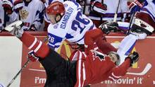Team Russia's Ildar Isangulov (26) and Canada forward Boone Jenner (20) fight for control of the puck during second period semi-final IIHF World Junior Championships hockey action in Calgary, Alta., on Tuesday. (Nathan Denette/The Canadian Press)