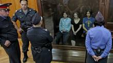 Nadezhda Tolokonnikova, right, Yekaterina Samutsevich, left, and Maria Alekhina, center, members of feminist punk group Pussy Riot seen behind a glass wall at a court in Moscow, Russia, Friday, Aug. 17, 2012. (Mikhail Metzel/AP)