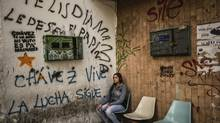 "Angela Perez, sits in a corner called ""Misery Corner"" with political graffiti in Spanish that reads, ""Chavez lives, the fight continues"" in Caracas, Venezuela, June 1, 2013. The city today, where some corners have names that people use as landmarks, is a traffic-choked, graffiti-smeared, hyperbolically violent capital where spasmodic bouts of modernization and growth over the years have left little of the charm of some other South American cities. (MERIDITH KOHUT/NYT)"