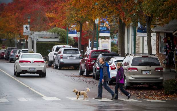 A couple walks along Second Street in Qualicum Beach.