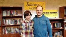 Viktor and Inna Bisovetskyi pose in the library they have started for protesters near Independence Square in Kiev. The sign directly behind them reads 'Library of Maidan.' The other sign says 'After you've read them return them.' (The Globe and Mail/Paul Waldie)