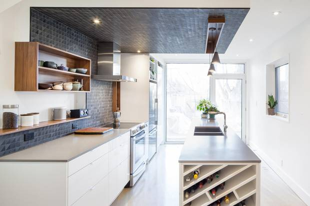 The kitchen is clad in the same basalt tile as the fireplace, creating a visual wrap.