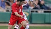 Canada's Russell Telbert (11) battles Denmark's Henrik Dalsgaard (20) during the second half of a friendly soccer match on Jan. 26, 2013, in Tucson, Ariz. (John Miller/The Associated Press)