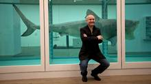 """British artist Damien Hirst poses for photographers beside the 1991 piece """"The Physical Impossibility of Death in the Mind of Someone Living"""", a tiger shark preserved in formaldehyde in a vitrine, during a media preview of the first substantial survey show of his work in the UK at the Tate Modern gallery in London, Monday, April 2, 2012. (Matt Dunham / AP/Matt Dunham / AP)"""