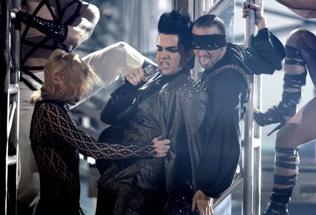 American Idol alum Adam Lambert (right) brought a millennial sense of glam to his performances, including a sparkling suit worn during his notorious performance at the American Music Awards in 2009, though he now sports a more toned down look.