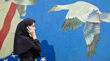 A Iranian woman talks on her mobile phone while passing the former U.S. embassy in Tehran in November of 2008. (MORTEZA NIKOUBAZL/REUTERS)