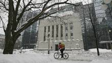 A cyclist passes the Bank of Canada building through a snow-covered sidewalk in Ottawa in this file photo. (Chris Wattie/Reuters)