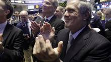 CBS President and CEO Leslie Moonves, right, and CBS Outdoor Americas Inc. CEO Jeremy Male, center, applaud on the floor of the New York Stock Exchange, as CBS Outdoor's IPO begins trading, Friday, March 28, 2014. (Richard Drew/AP)