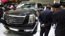 In this April 22, 2008 file photo, visitors look at a Cadillac Escalade SUV at the Auto China 2008 auto show in Beijing (Greg Baker)