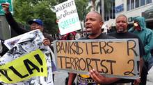 A man holds a placard equating bankers with terrorists as a small group of protesters march past banks in downtown Los Angeles on October 19, 2011. (FREDERIC J. BROWN/AFP/Getty Images)