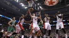 Boston Celtics forward Kelly Olynyk, left, can only watch as Toronto Raptors, from left, Kyle Lowry, Tyler Hansbrough and DeMar DeRozan go for a rebound at the Air Canada Centre in the Raptors season-opener on Wednesday night. (Frank Gunn/THE CANADIAN PRESS)